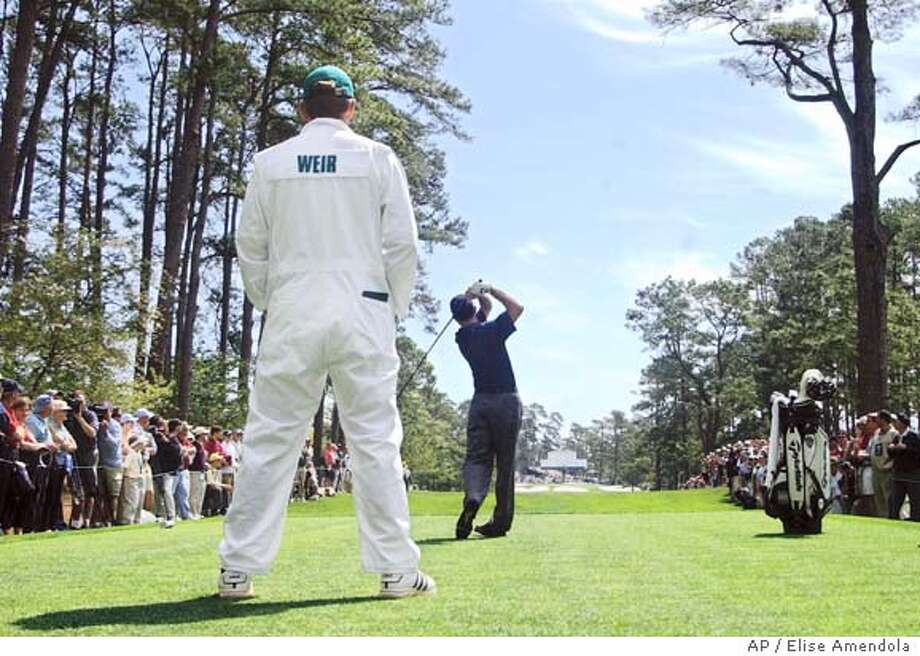 Mike Weir, from Canada, the defending champion hits from the seventh tee as his caddy looks on during practice for the golf tournament at the Augusta National Golf Club in Augusta, Ga., Tuesday, April 6, 2004. AP Photo/ Elise Amendola Photo: ELISE AMENDOLA