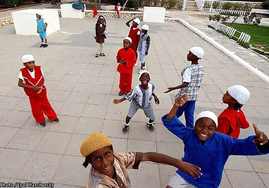 TO GO WITH STORY BY DANIELLE HASS--- Children from the Black Hebrew Community play in a playground in a communal area amidst the bungalows that have been home to the group for the past 32 years in Dimona Monday Oct 21 2002. The children, who have just finished school, cover their heads, as a sign of respect for their teachers. PHOTO BY Eyal Warshavsky/BAUBAU Photo: EYAL WARSHAVSKY