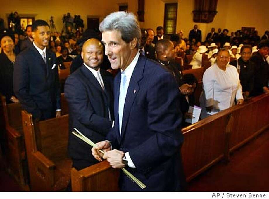 Democratic presidential candidate Sen. John Kerry, D-Mass., center, holds palm branches as he departs Charles St. AME Church, in Boston's Roxbury district, Sunday, April 4, 2004, following Palm Sunday services. Kerry attended the services on the anniversary of Martin Luther King's assassination. (AP Photo/Steven Senne) #######0421705756 Photo: STEVEN SENNE