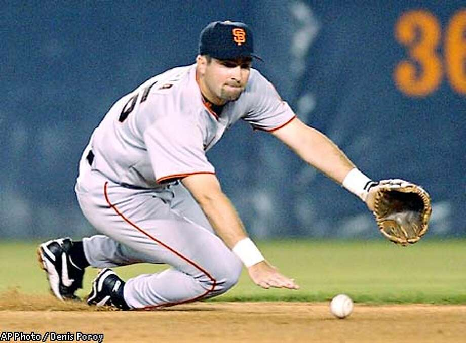 San Francisco Giants shortstop Rich Aurillia slides to his knees as he makes the stop on a ball hit by the San Diego Padres Ramon Vazquez during the first inning Thursday, Sept. 12, 2002 in San Diego. (AP Photo/Denis Poroy) Photo: DENIS POROY