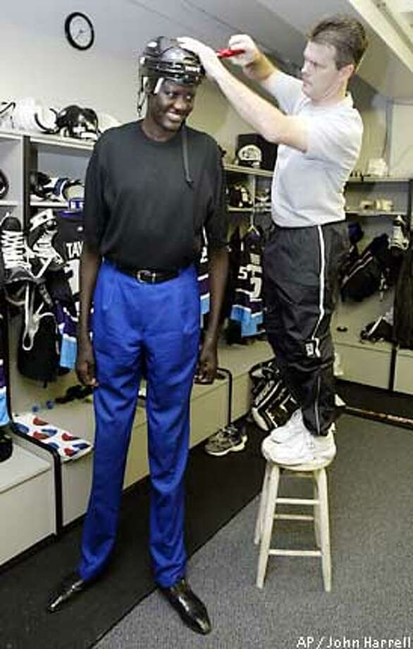 Former NBA player Manute Bol, left, has a hockey helmet adjusted by Indianapolis Ice equipment manager Darrin Flinchem, Friday, Nov. 15, 2002 in Indianapolis. Bol will be playing for the Ice in their game Saturday night, Nov. 16, against the Amarillo Rattlers to raise money for the Ring True Foundation. A foundation run by Bol to aid displaced Sudanese. (AP Photo/John Harrell) Photo: JOHN HARRELL