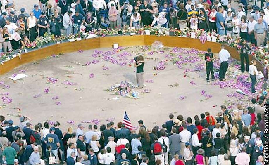 In the center of ground zero, a wooden circle was constructed where families could lay flowers and memorabilia...but soon families started entering the center of the circle...these two women hugged after placing a flag. By Brant Ward/Chronicle Photo: BRANT WARD