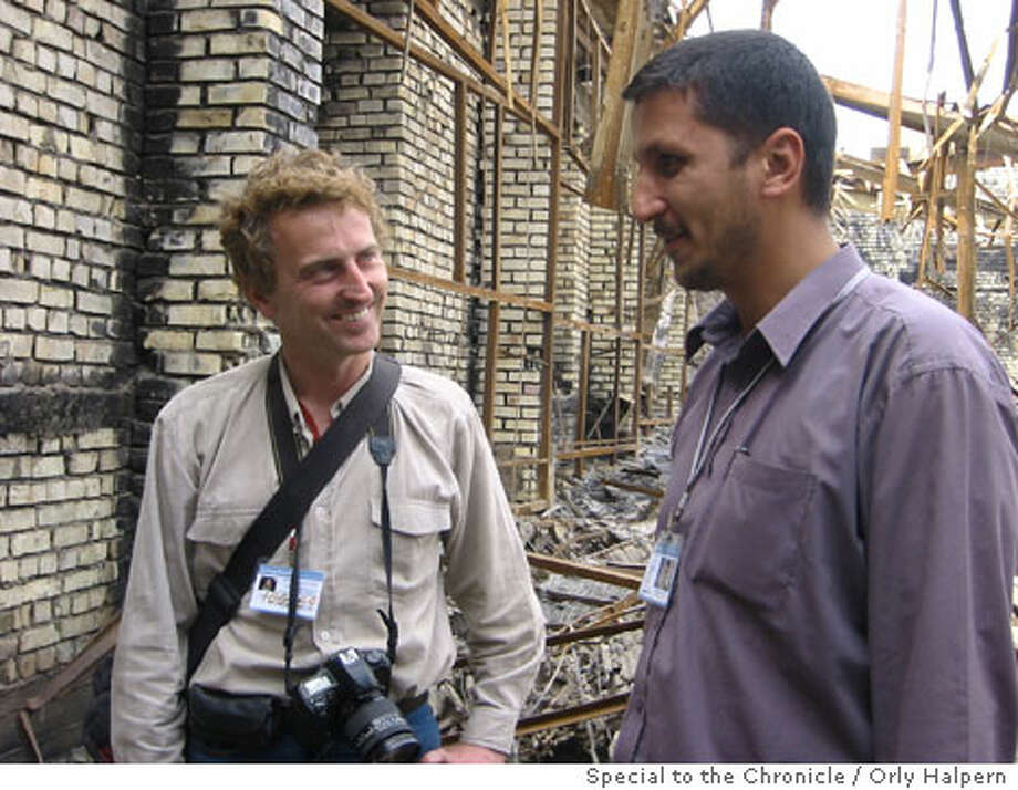 Sean O'Sullivan, left, talks with one of the 1,100 Iraqis that JumpStart employs to clean bombed-out and burned sites in Baghdad. Photo by Orly Halpern, special to the Chronicle
