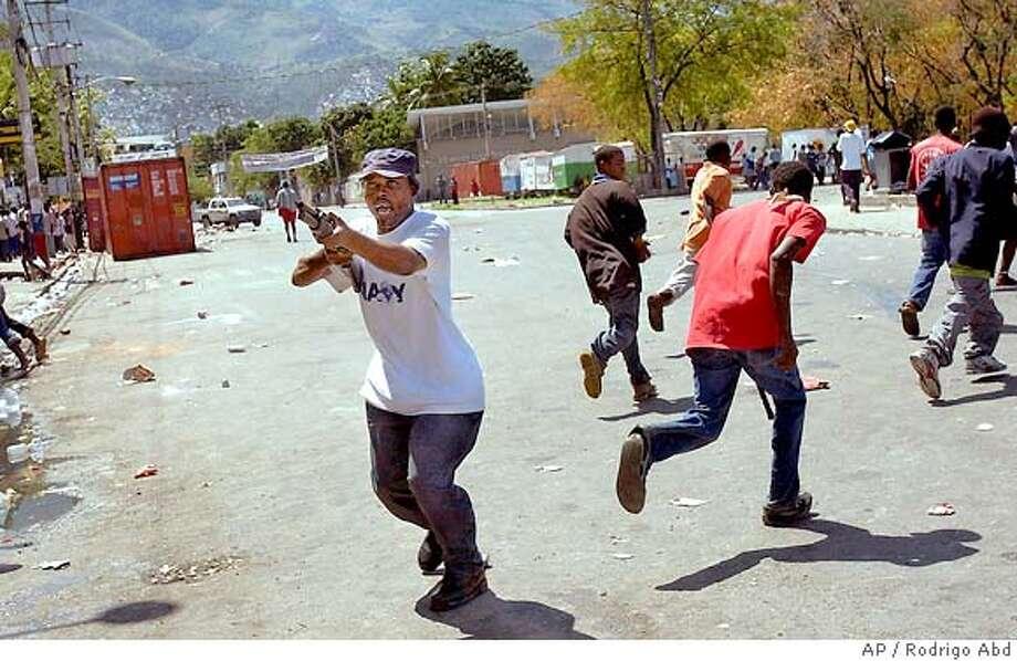 An armed supporter of Haitian President Jean-Bertrand Aristide roams the streets of Port-au-Prince after his departure, Sunday, Feb. 29, 2004. (AP Photo/Rodrigo Abd) Photo: RODRIGO ABD