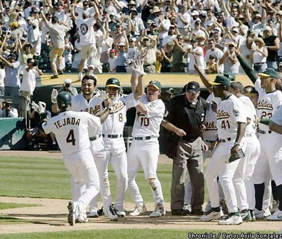 ATHLETICS02A-C-01SEP02-SP-CG --- As fans dance on the Twins's dugout, Oakland Athletics shortstop, Miguel Tejada, left, is greeted at home by teammates, l-r, Eric Chavez, Randy Velarde, Scott Hatteberg, (3B coach) Ron Washington, Olmedo Saenz, and David Justice, after Tejada blasted a three-run walk-off homerun in the bottom of the ninth inning against the Minnesota Twins on Sunday, September 2, 2002. The Athletics won by a score of 7-5, their 18th consecutive win, which breaks a franchise record.  (CARLOS AVILA GONZALEZ/SAN FRANCISCO CHRONICLE)