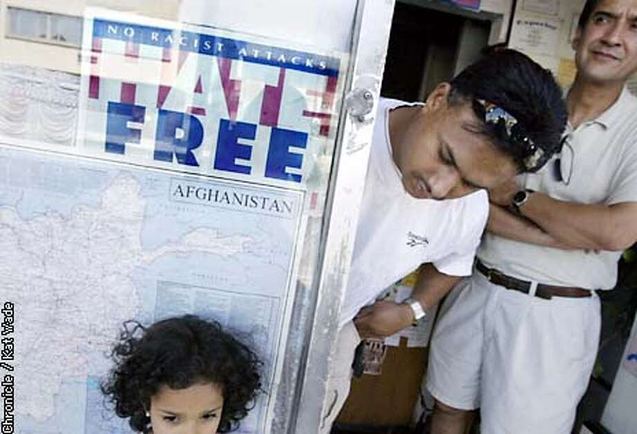 "SPECIAL1a-C-02SEP02-MT-KW - James Farid (CQ) (Center) checks on his daughter Sabreena (CQ) Farid, 4, as she stands beneath a sign that reads HATE FREE No Racist Attacks in the window of de Afghan Kabob House in ""little Kabul"" in Fremont. In the background, Kabul born, Mohammad (CQ) Fakhri (CQ) (Right) peers down Fremont Blvd. SAN FRANCISCO CHRONICLE PHOTO BY KAT WADE"