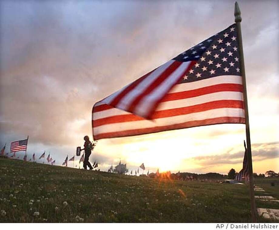 Cynthia O'Sandon, of Mount Holly, N.J., is silhouetted near a U.S. flag as she carries flowers to her father's grave at Brigadier Gen. William C. Doyle Veterans Memorial Cemetery in Arneytown, N.J., Friday, May 28, 2004. O'Sandon's father, Clifford B. Chase, was in the Army during World War II. (AP Photo/Daniel Hulshizer) Photo: DANIEL HULSHIZER