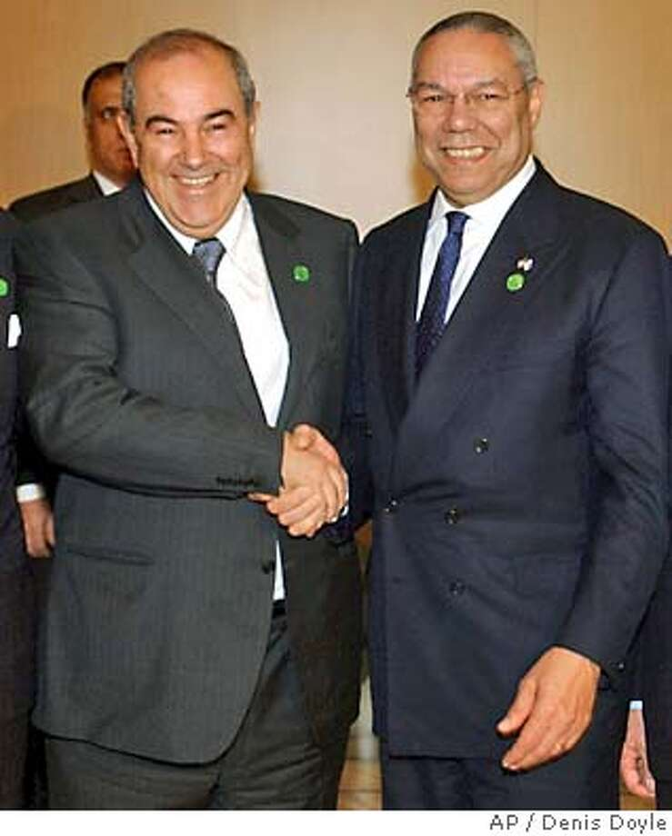 ** FILE ** U.S. Secretary of State Colin Powell, right, greets Dr. Iyad Allawi, President of the U.S.-appointed Iraqi Governing Council, during the International Donor's Conference in Madrid for the Reconstruction of Iraq, in this Oct. 23, 2003 file photo. Iyad Allawi, a Shiite Muslim physician who spent years in exile, has been nominated by the Governing Council to become prime minister of the new government to take power June 30, a council member said in Baghdad, Iraq, Friday, May 28, 2004. (AP Photo/Denis Doyle, file) Photo: DENIS DOYLE
