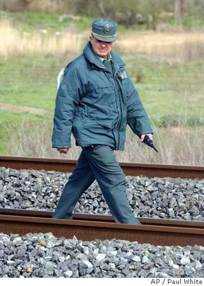 A civil guard checks the rail tracks after a bomb was found on the track of the high speed Madrid to Seville AVE train tracks in Mocejon, some 40 miles (60km) south of Madrid, Spain, Friday April 2, 2004. (AP Photo/Paul White) Photo: PAUL WHITE