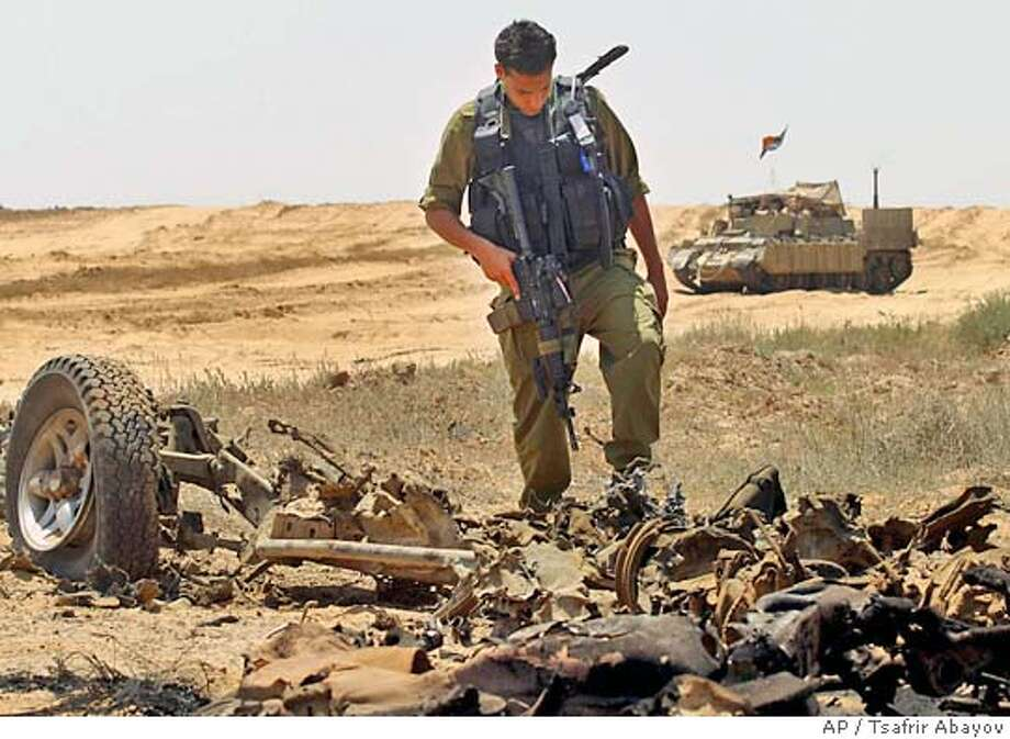 An Israeli soldier looks at the remains of a car bomb that exploded earlier in the day, near an Israeli convoy on the Gaza-Egypt border, killing a Palestinian attacker and lightly wounding two soldiers, at Safa checkpoint, Friday, May 28, 2004. Israeli (AP Photo/Tsafrir Abayov) Photo: TSAFRIR ABAYOV
