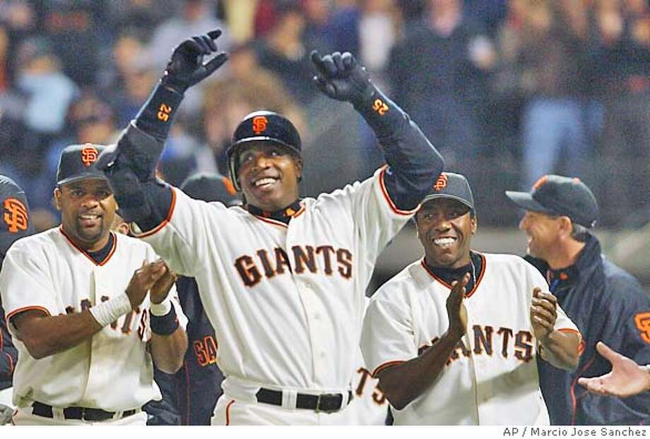 San Francisco Giants' Barry Bonds, middle, celebrates with teammates Neifi Perez, left, and Deivi Cruz, right, after hitting a two-run home run to win the game against the Colorado Rockies in the ninth inning on Friday, May 28, 2004, in San Francisco. Giants won, 4-2. (AP Photo/Marcio Jose Sanchez) Photo: MARCIO JOSE SANCHEZ
