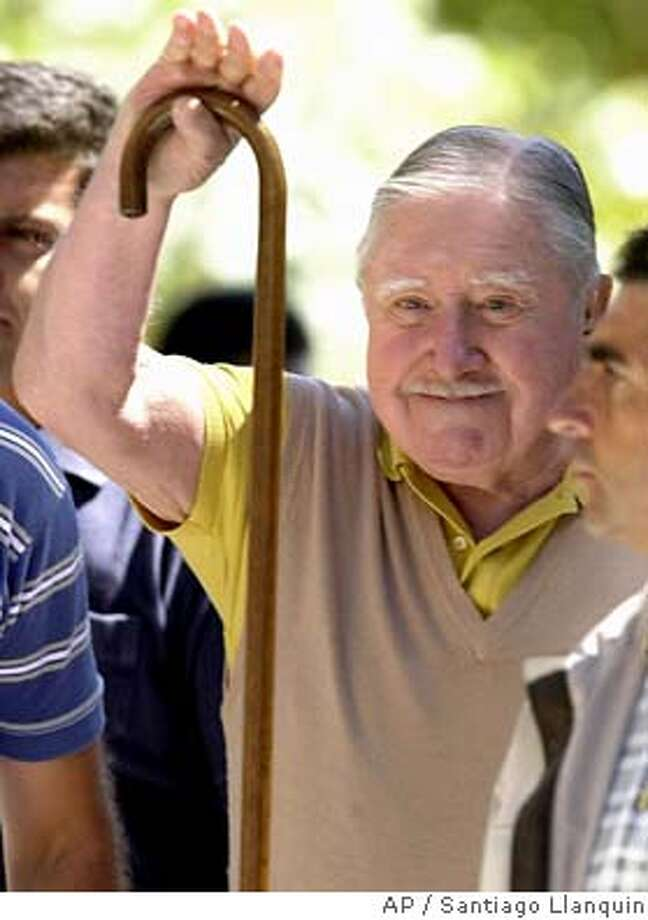 ** FILE ** Chilean former dictator Gen. Augusto Pinochet waves to supporters in this March 11, 2001 file photo in his countryside residence of Bucalemu. A Chilean court Friday stripped former dictator Augusto Pinochet of his immunity from prosecution, paving the way for his trial on human rights charges in Santiago, Chile, Friday, May 28, 2004. (AP Photo/Santiago Llanquin, File) Photo: SANTIAGO LLANQUIN