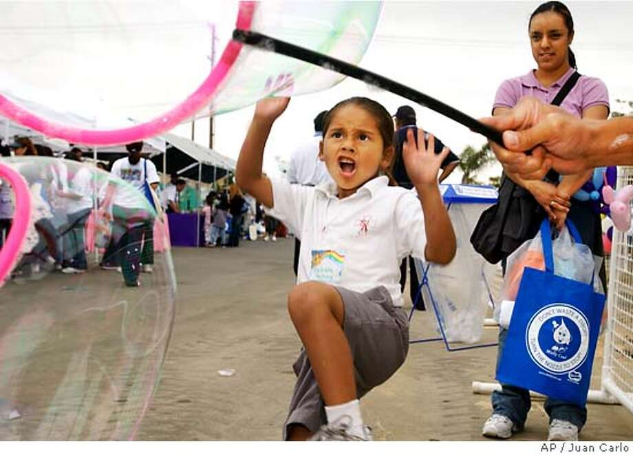 Celeste Martinez, 5, who's in kindergarter at St.Anthony's school in Oxnard, Cali. karates kicks the water bubble as Nohemi Ramos parent volunteer watches at the Oxnard�s second annual Children�s Water Science Festival at the Oxnard Water Yard . (AP Photo/Ventura County Star, Juan Carlo)
