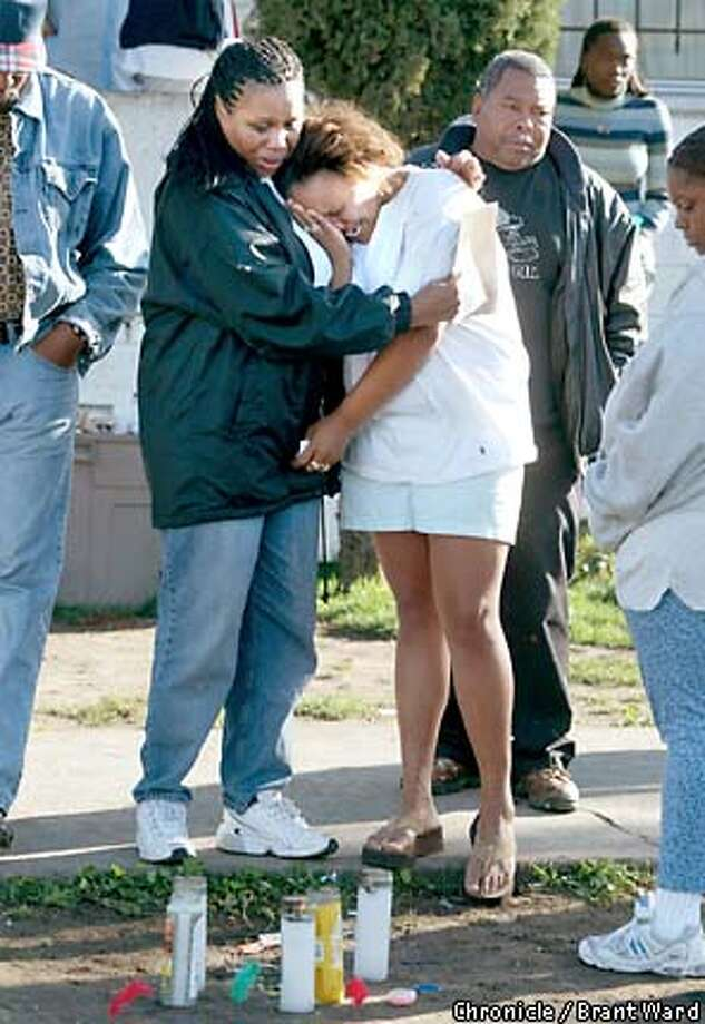 Roneisha Tillman, right in white, is comforted by Betty McCullough in front of the home of Tamellia Cobbs in east Oakland Monday after the 15 year old was gunned down. Tillman is the girl's cousin while McCullough was Tamellia's aunt. They stand at a small memorial for the child at the place she died. Other family and friends are not identified. By Brant Ward/Chronicle Photo: BRANT WARD