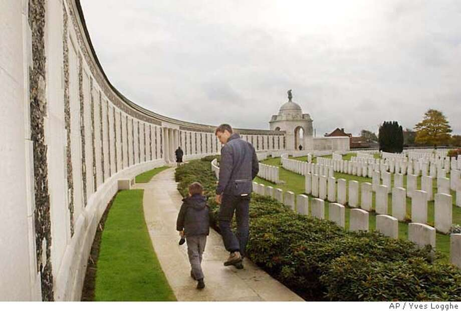 **ADVANCE FOR SUNDAY, NOV. 9** A father and his son walk along a colonnade at Tyne Cot cemetery, the largest British war cemetery in the world, in Passchendaele, Belgium, Oct. 31, 2003. About 11,908 graves are registered on the cemetery of which 70 percent are unknown. (AP Photo/Yves Logghe) A view of the fields surrounding the Croonaert Chapel war cemetery in Wijtschate, near Ypres, Belgium, where some of World War I's most murderous trench warfare took place. Photo: YVES LOGGHE