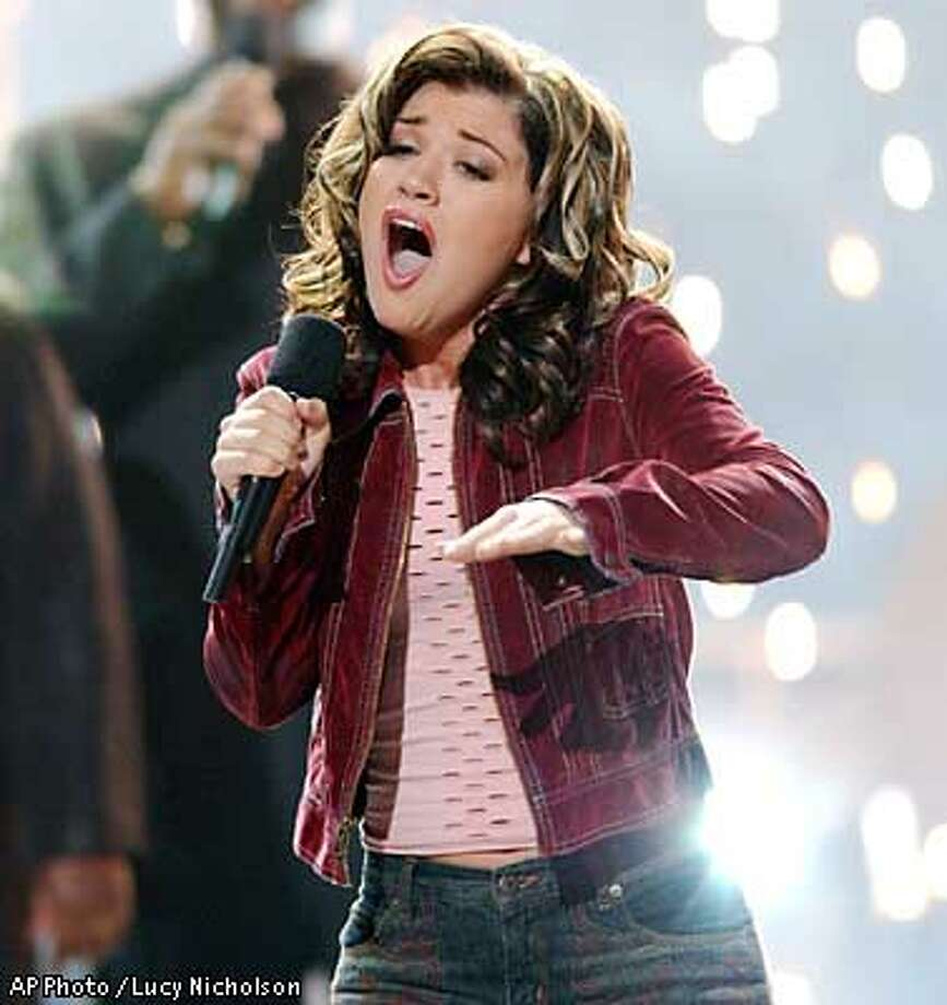 """** ADVANCE FOR MONDAY, SEPT. 9 ** Kelly Clarkson, 20, of Burleson, Texas, sings after winning Fox's television talent contest, """"American Idol,"""" in Los Angeles Wednesday, Sept. 4, 2002. Nearly 28 million people, mostly young viewers, were watching when Clarkson won, making it the hit show of the summer. (AP Photo/Lucy Nicholson) Photo: LUCY NICHOLSON"""