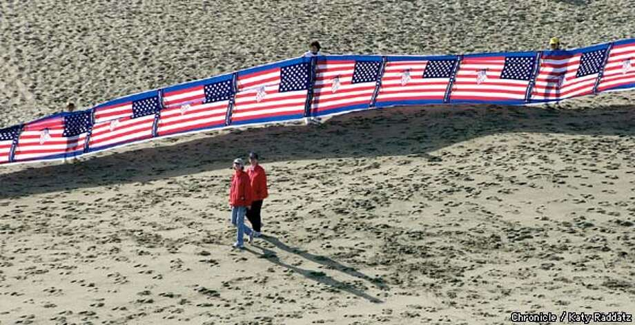 PHOTO BY KATY RADDATZ--THE CHRONICLE  World's largest, or at least, longest, flag, made by stitching together about 5,000 American flags,end to end. SHOWN: the banner on the east side of the GG Bridge. Photo: KATY RADDATZ