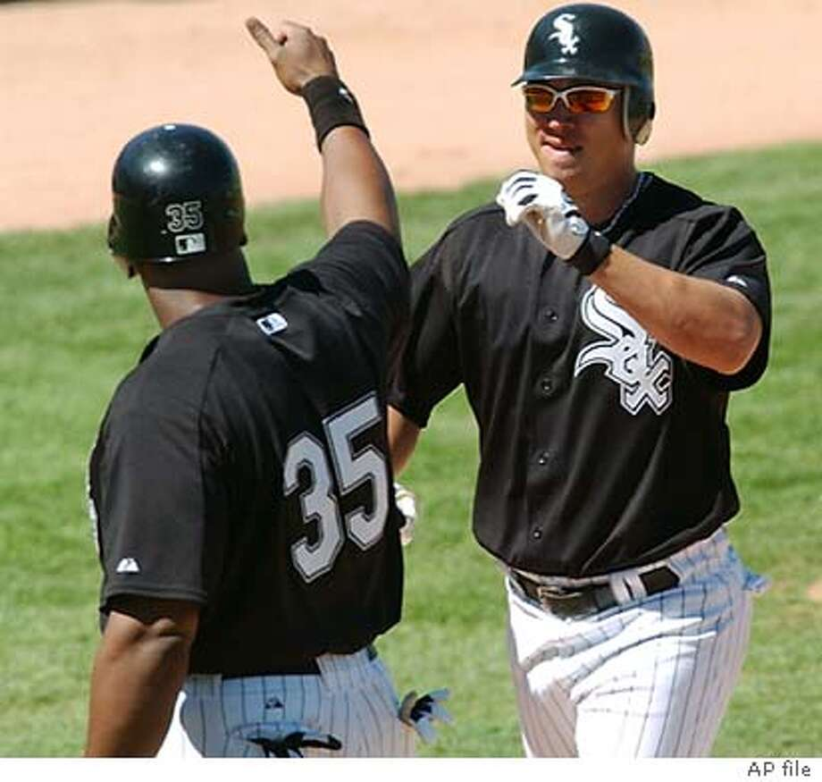 Chicago White Sox right fielder Magglio Ordonez, right, is congratulated by teammate Frank Thomas (35) after Ordonez hit a two-run home run in the first inning of a spring training game against the Colorado Rockies in Tucson, Ariz., Monday, March 15, 2004. The Rockies won 7-5. (AP Photo/Ed Andrieski) ProductName	Chronicle Photo: ED ANDRIESKI