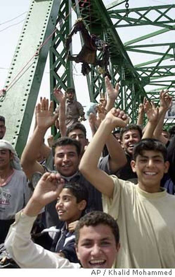 ** EDS NOTE GRAPHIC CONTENT **Iraqis chant anti-American slogans on a bridge over the Euphrates River where charred bodies are hanging in Fallujah, west of Baghdad, Wednesday March 31 2004. Enraged Iraqis in this hotbed of anti-Americanism killed four foreigners Wednesday, including at least one U.S. national, took the charred bodies from a burning SUV, dragged them through the streets, and hung them from the bridge spanning the Euphrates River. (AP Photo/Khalid Mohammed) Photo: KHALID MOHAMMED