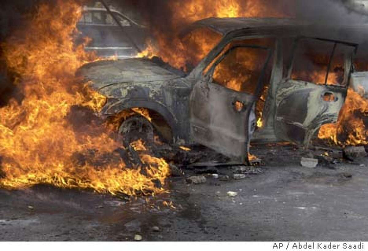 Flames engulf a vehicle in Fallujah, west of Baghdad, Wednesday March 31, 2004. Gunmen in Fallujah attacked two civilian cars that residents said were carrying up to eight foreign nationals. The occupants of the cars were killed and their vehicles were set on fire. (AP Photo/Abdel Kader Saadi)