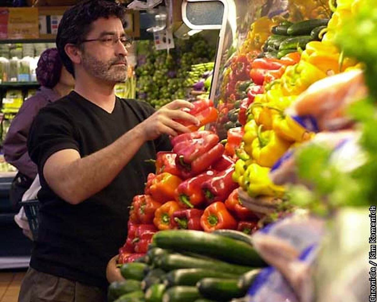 Whole Foods Produce buyer James Parker inspects peppers in the produce section of their San Francisco store. Photo by Kim Komenich/ The Chronicle