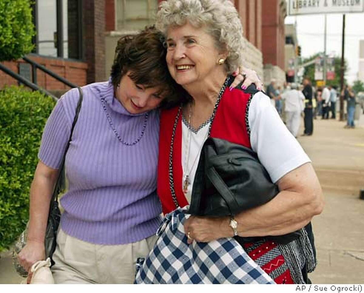 Diane Leonard, left, who lost her husband, Don, in the Oklahoma City bombing, embraces Sharon Davis, right, who lost her daughter, Kathy Seidl, as they walk away from the Pittsburg County courthouse in McAlester, Okla., Wednesday, May 26, 2004, after convicted Oklahoma City bombing conspirator Terry Nichols was found guilty of 161 state murder charges in the 1995 bombing. (AP Photo/Sue Ogrocki)