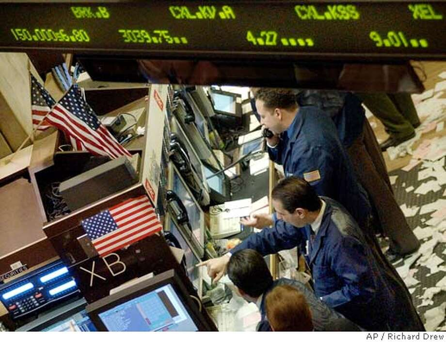 Stock quotations scroll above workers at a booth on the floor of the New York Stock Exchange, Wednesday March 24, 2004. Terrorism fears and a record antitrust fine for Microsoft Corp. weighed on Wall Street Wednesday, sending blue chips lower despite a better-than-expected manufacturing report. (AP Photo/Richard Drew) Stock quotations scroll above workers at a booth on the floor of the New York Stock Exchange Wednesday, where blue chips sank but the Nasdaq managed to stay positive. Stock quotations scroll above workers on the floor of the New York Stock Exchange, where the first quarter of 2004 ended on a down note for the Dow and the Nasdaq and a slight uptick for the S&P. Photo: RICHARD DREW