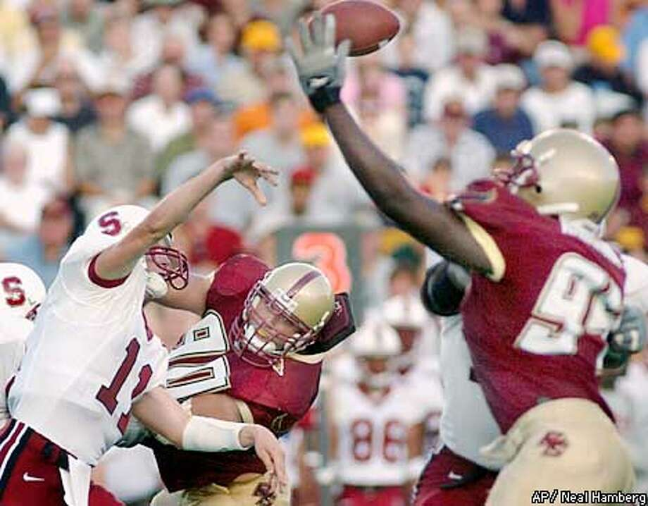 Stanford quarterback Kyle Matter (11) lets a pass fly under pressure from Boston College defensive tackle Tom Martin (90) and defensive end Mathias Kiwanuka (94) during the fourth quarter Saturday, Sept. 7, 2002, in Boston. Stanford won 34-27. (AP Photo/Neal Hamberg) Photo: NEAL HAMBERG