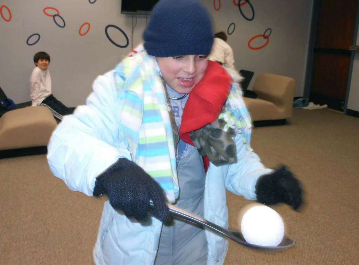 """Jack Hernandez, 9, competes in a snow clothes relay Friday at the Fairfield Woods Branch Library, which required him to dress in several layers of winter clothes and shuttle a styrofoam """"snowball"""" on a spoon."""