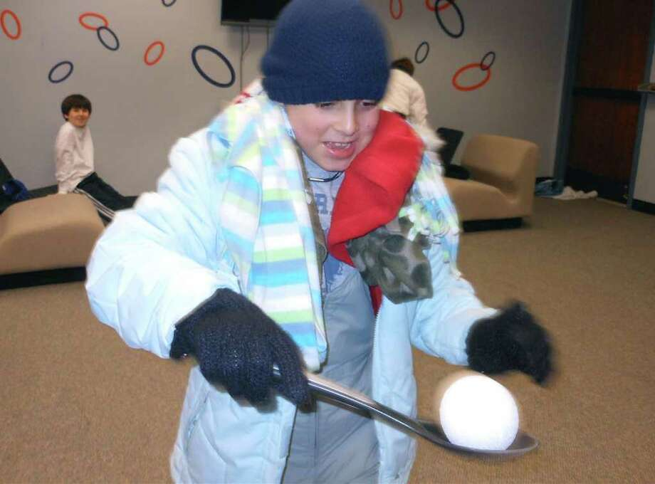 "Jack Hernandez, 9, competes in a snow clothes relay Friday at the Fairfield Woods Branch Library, which required him to dress in several layers of winter clothes and shuttle a styrofoam ""snowball"" on a spoon. Photo: Mike Lauterborn / Fairfield Citizen contributed"
