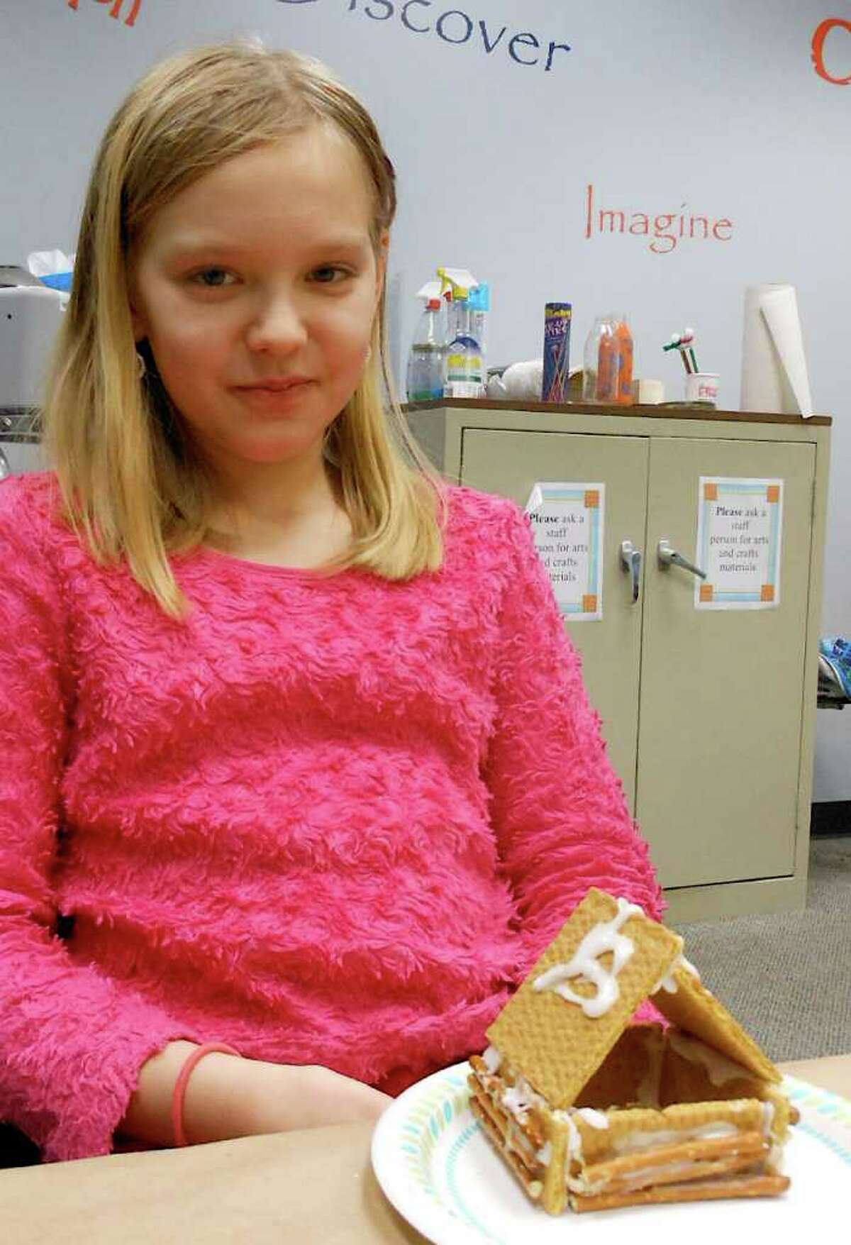 """Nadia Roshenets, 10, sits with her completed edible log cabin at the """"Cabin Fever"""" program Friday at the Fairfield Woods Branch Library."""