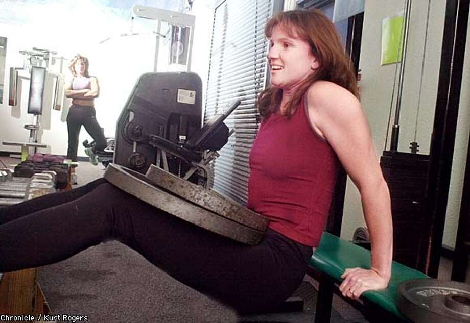 Jeanne Watts works out at the Pacifica Athletic Center as Alene Brisbane looks on. They will be competing in a world championship weightlifting event next week. Chronicle photo by Kurt Rogers