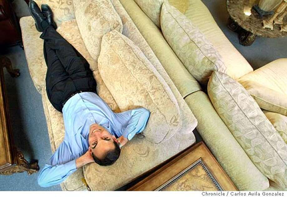 Frank Romero, design consultant at Pillow Park in Alameda, Ca., isn't really lying down on the job...he's demonstrating how to best pick out a couch. Romero and other consultants at the furniture store actually encourage customers to lie down, read a book, some even snooze on the couches in the showroom, all to find a sofa that feels right. Romero is shown here in the showroom on Thursday, May 20, 2004. Photo taken on 05/20/04 in Alameda, Ca. Photo By Carlos Avila Gonzalez / The San Francisco Chronicle Photo: Carlos Avila Gonzalez
