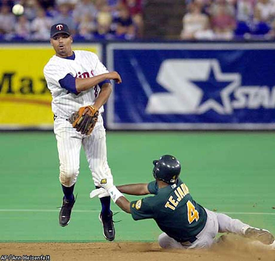 Minnesota Twins shortstop Luis Rivas, left, throws to first base to turn a double play after forcing Oakland Athletics' Miguel Tejada (4) at second in the sixth inning in Minneapolis, Friday, Sept. 6, 2002. The Athletics' Jermaine Dye was out at first base. (AP Photo/Ann Heisenfelt) Photo: ANN HEISENFELT