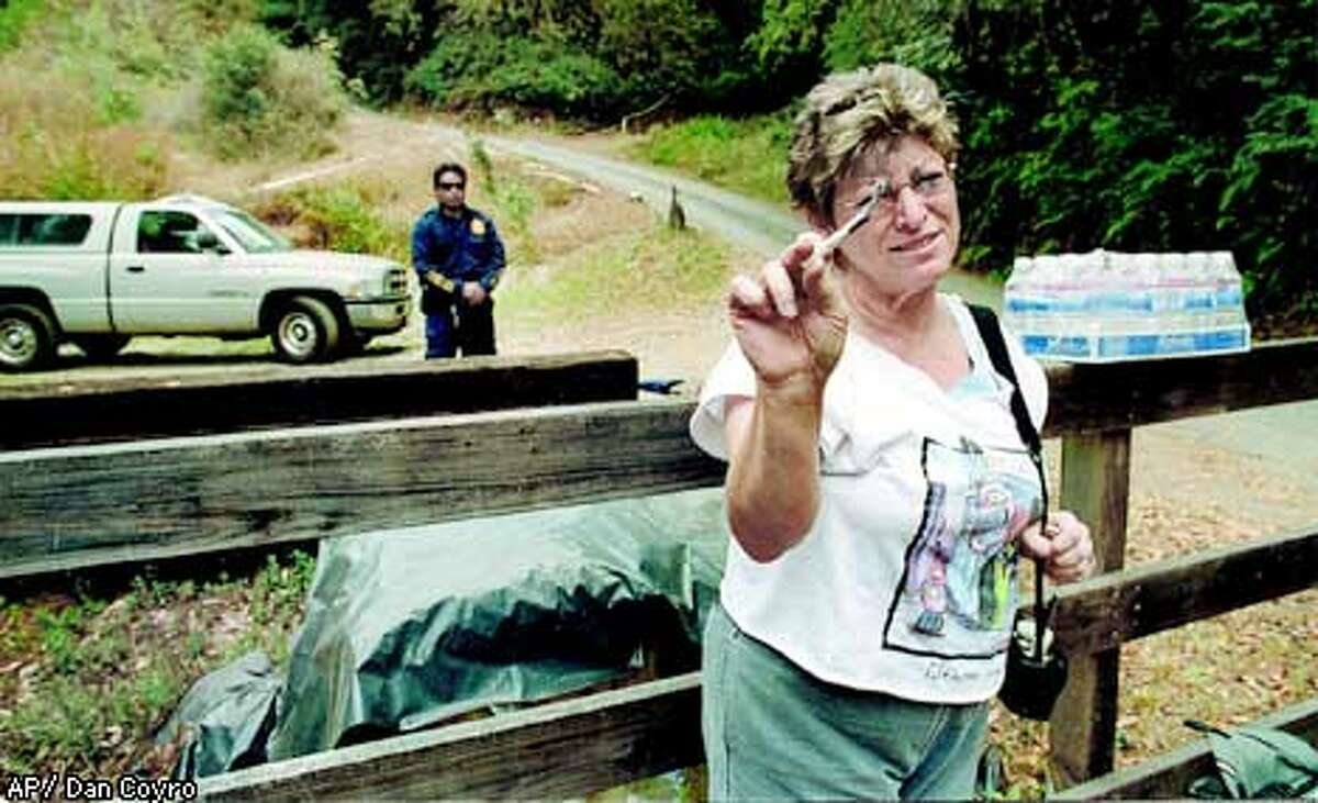 Jean Hanamoto smokes what she says is a marijuana cigarette she is using for medical purposes, as a Drug Enforcement Administration agent stands in the background, guarding an entrance to Valerie and Michael Corral's marijuana farm, north of Santa Cruz, Calif., Thursday, Sept. 5, 2002. Hanamoto was one of several members of Wo/Men's Alliance for Medical Marijuana who came to the farm to protest the arrests. Federal agents raided the marijuana farm and arrested the owners, who helped write the state law legalizing medical use of the plants. (AP Photo/Santa Cruz Sentinel, Dan Coyro)