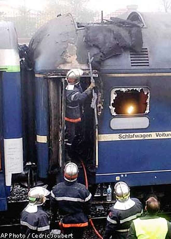 Firefighters work on the coaches of the Paris-Vienna overnight express train that caught fire near Nancy, eastern France, early Wednesday Nov. 6, 2002, killing 12 passengers and injuring nine. Authorities were initially attributing the cause of the fire to a possible electrical problem in the heating system. (AP Photo/Cedric Joubert) Photo: CEDRIC JOUBERT