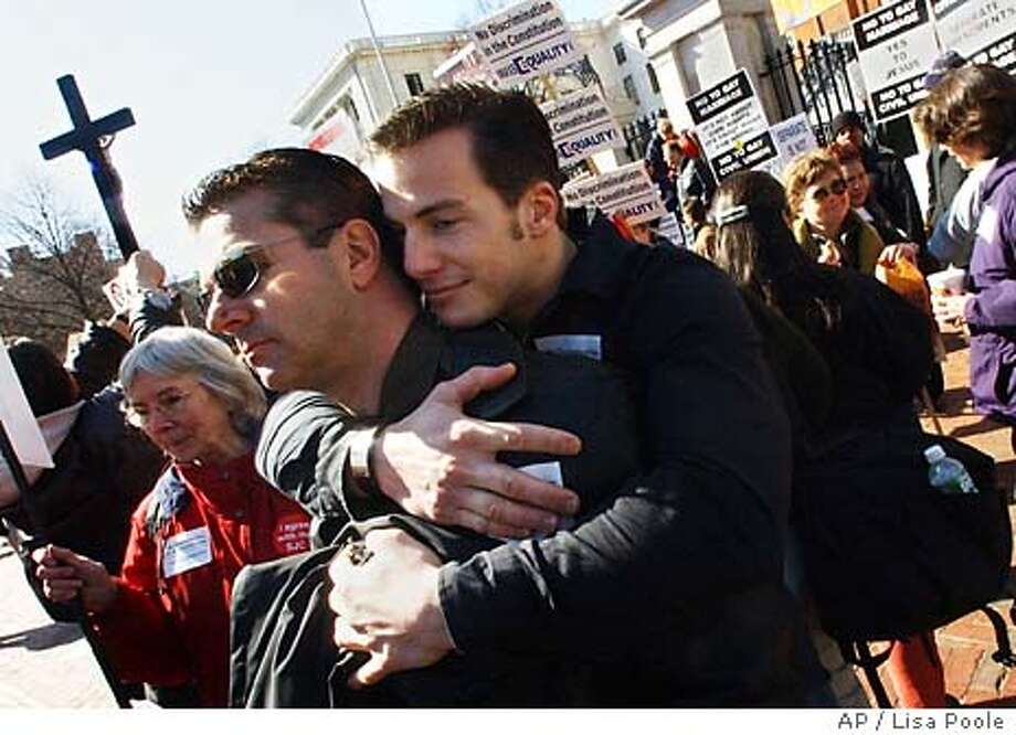 Seth Riker, right, hugs his partner Greg Farnkoff, both from Cotuit, Mass., outside the Statehouse as the constitutional convention continued to debate the gay marriage issue, Monday, March 29, 2004, in Boston. (AP Photo/Lisa Poole) Photo: LISA POOLE