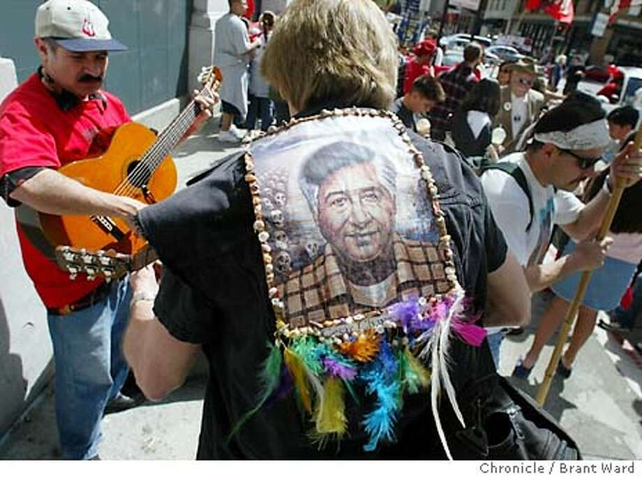 parade011_bw.jpg Guitarist Francis Collins jammed with friends at the parade...he wore a likeness of Chavez on his back for the event.  The Cesar E. Chavez holiday parade and festival 2004 began with a march down Market Street at noon Sunday...although the crowds were disappointing, there was plenty of spirit with the marchers. BRANT WARD / The Chronicle Photo: BRANT WARD