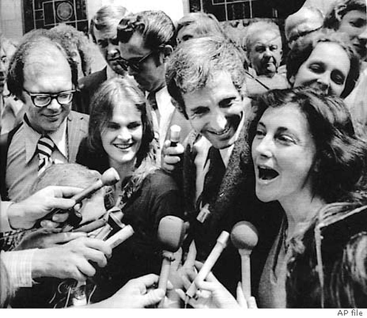 ANTHONY RUSSO, LEFT, AND DANIEL ELLSBERG, THE CO-DEFENDANTS IN THE LENGTHY PENTAGON PAPERS TIAL, TALK TO NEWSMEN WITH THEIR HAPPY WIVES OUTSIDE THE FEDERAL BUILDING IN LOS ANGELES FRIDAY AFTER ALL CHARGES AGAINST THEM WERE DISMISSED. RUSSO'S WIFE IS MS. KATHARINE BARKLEY, AND ELLSBERG'S WIFE IS PAT.