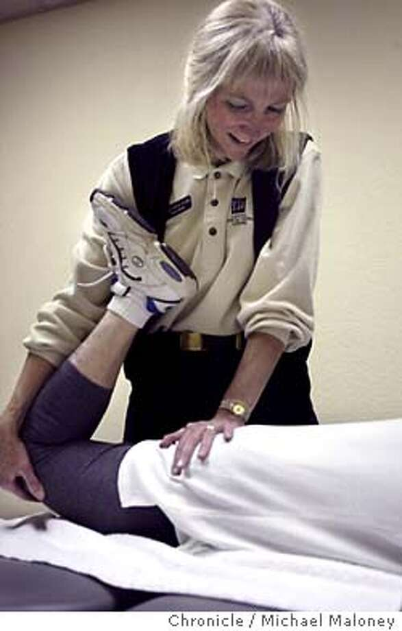 Physical therapist Robin Wham stretches patient Jeane (cq) Wall. (Note : Wall is NOT a worker's comp patient.  Photo is part of a package attempting to understand various players in the workers' compensation system. Robin Wham is a physical therapist at Capitol Physical Therapy Center in Sacramento who spends much of her time working with people injured on the job. Michael Maloney / CHRONICLE Photo: Michael Maloney