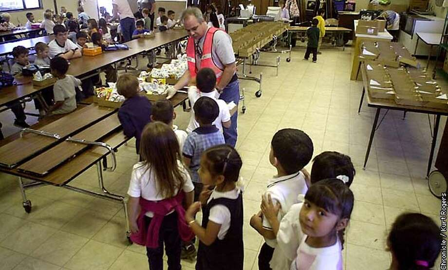 SKULBONDSB-C-30OCT02-MT-KR Vince Mazzori a volunteer with the school hands out lunches to the kids in five kindergarten classes  Measure H would rebuild the 50-year-old Fitch Mountain School, which lacks a multipurpose room so kids have to eat lunch in shifts in a double-wide portable classroom.  .Photo By Kurt Rogers