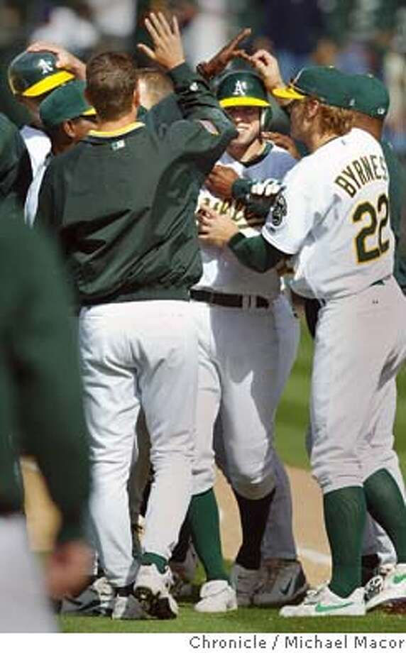 Oakland's Bobby Crosby is swarmed by teammates after hit single in the 12th inning scored the winning run to beat KAnsas city. The Oakland Athletics vs. Kansas City Royals. event on 5/22/04 in Oakland Michael Macor / San Francisco Chronicle Photo: Michael Macor