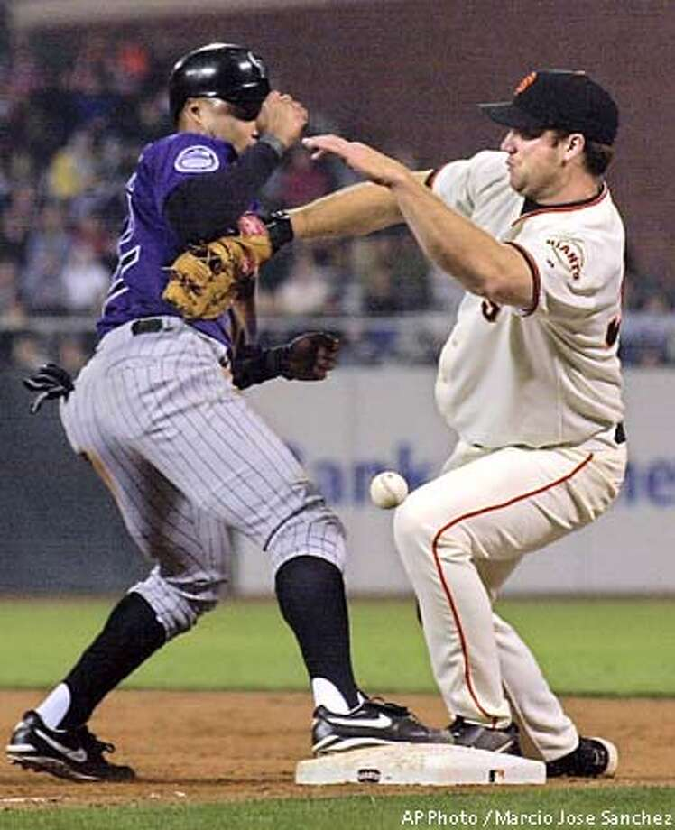 San Francisco Giants first baseman Damon Minor, right, bobbles the throw from the outfield after colliding with Colorado Rockies second baseman Terry Shumpert, left, following a fly out by Todd Helton in the third inning at Pacific Bell Park in San Francisco on Tuesday, Sept. 3, 2002. Shumpert reached second after the ball got past Minor. (  AP Photo / Marcio Jose Sanchez) Photo: MARCIO JOSE SANCHEZ