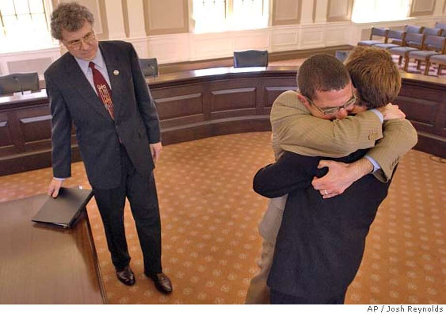 "Davin Moore, center, 36, and John ""Trey"" Watts III, both of Oklahoma City, Okla., who have been together for five years, embrace following a marriage ceremony performed by Somerville City Clerk, and Justice of the Peace, John Long, at left, in City Hall in Somerville, Mass. on Thursday, May 20, 2004. Moore and Watts rented a house and established residency in Northampton, Mass. out of concerns that Massachusetts would not allow out of state gay couples to marry. Somerville is one of four municipalities that refused to turn away out of state gay couples as requested by Massachusetts Gov. Mitt Romney. (AP Photo/Josh Reynolds) Photo: JOSH REYNOLDS"