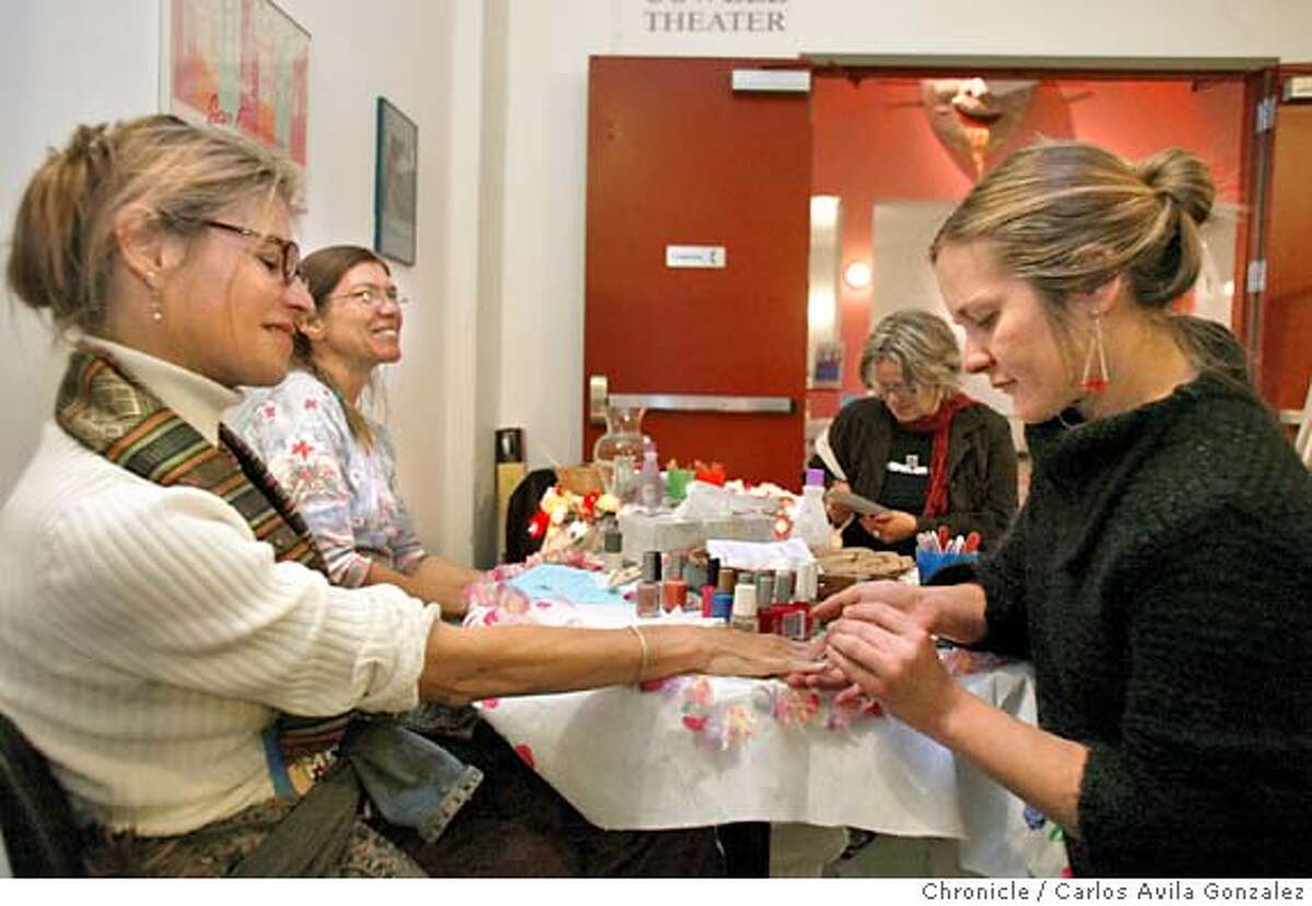 Lisa McCool, left, of Berkeley, gets her nails done by Fern Feto Spring, right, at Rally the Vote -- a major event to organize the estimated 50 million eligible women who did not vote in the last election -- The event took place at Fort Mason on Tuesday, May 18, 2004. The organizer is Joan Blades, who founded MoveOn.Org, which has become a leading 527 (independent expenditure) group aiming to organize voters in 2004. Other women's groups who will participate include MOB (Mothers Opposed to Bush) and a variety of other groups -- story will talk about if women (particularly moms) see this election differently because of the war... Photo taken on 05/18/04 in San Francisco, Ca. Photo By Carlos Avila Gonzalez / The San Francisco Chronicle