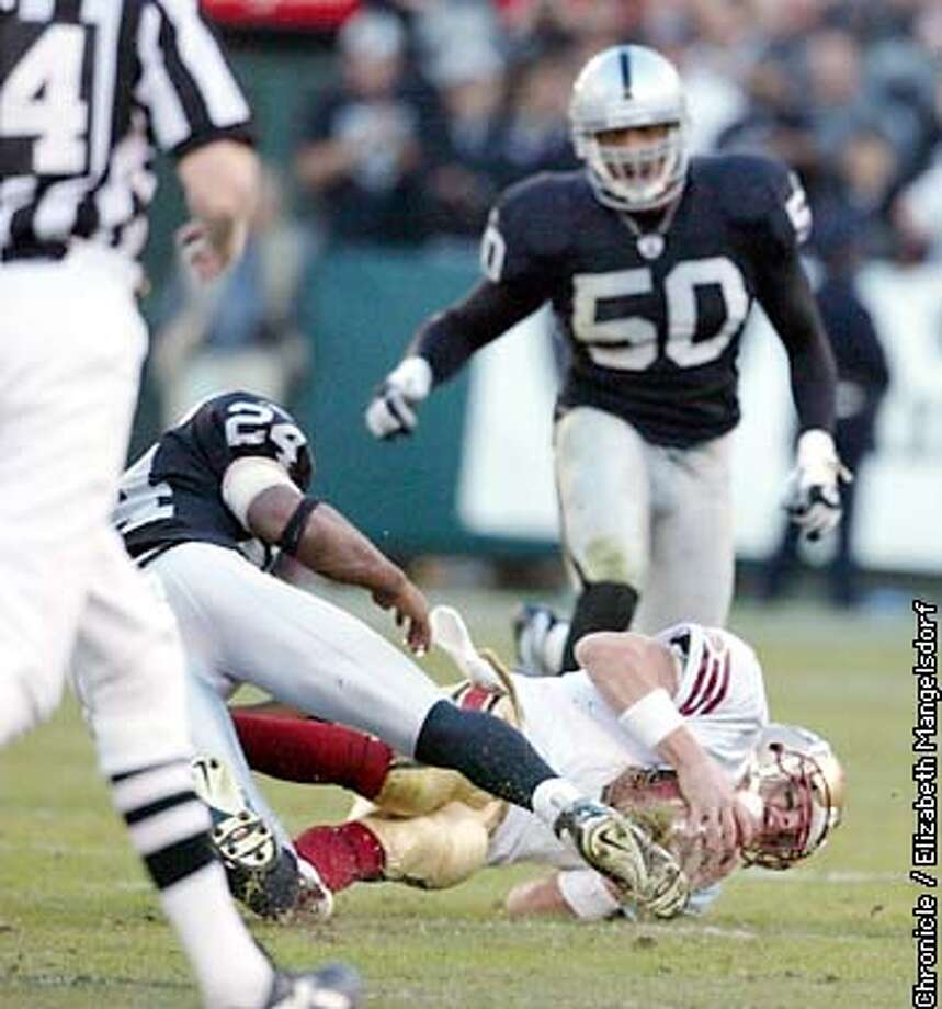 RAIDERS04b-C-03 NOV02-SP-LM Niners beat the Raiders at the Oakland coliseum.  Jeff Garcia is brought down by raider #24 charles Woodson on one of his runs during the Overtime period.  Chronicle Photo by Liz Mangelsdorf. Photo: Liz Mangelsdorf
