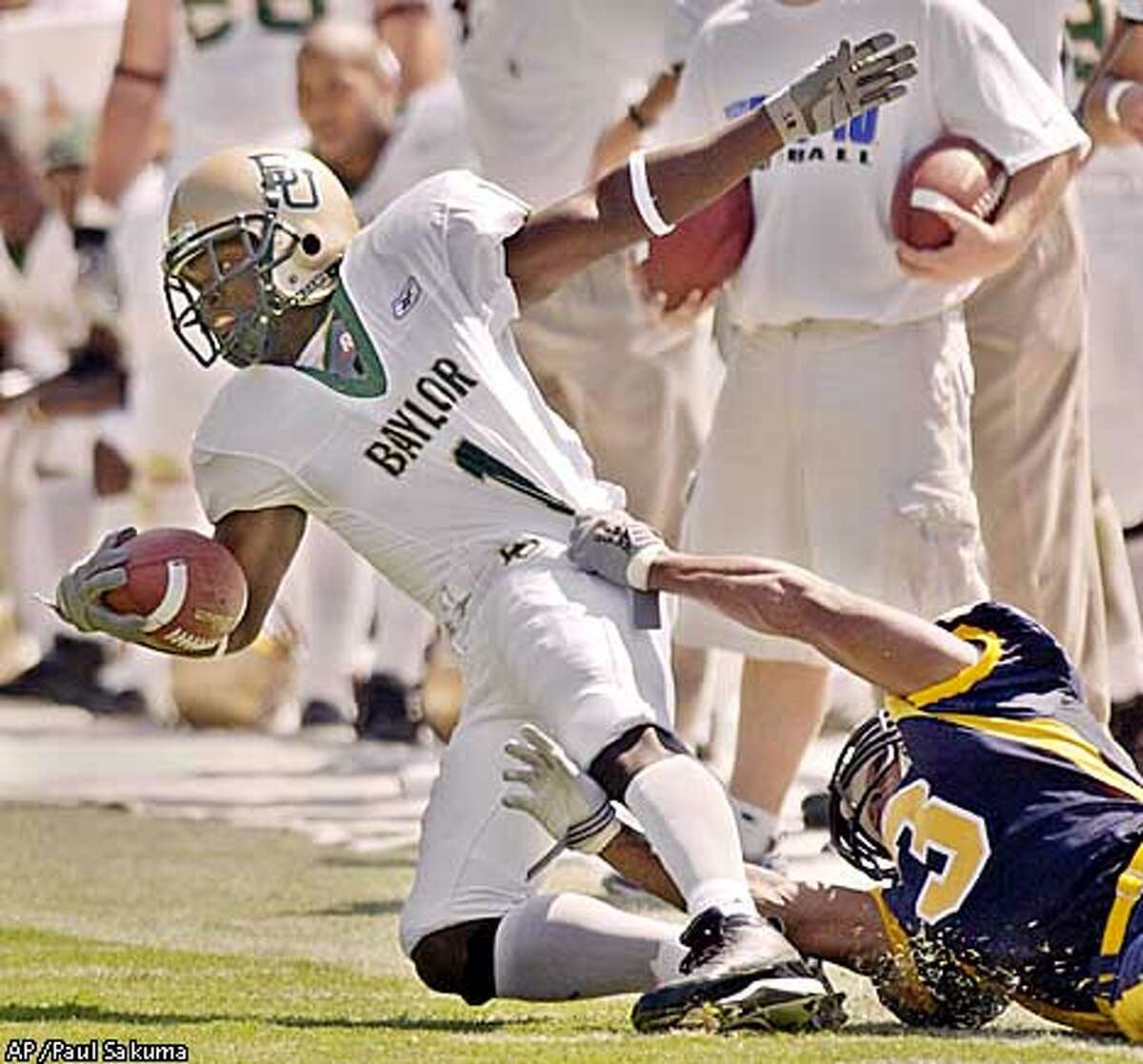 Baylor wide receiver Marques Roberts finds himself in the clutches of Cal's James Bethea. Associated Press photo by Paul Sakuma