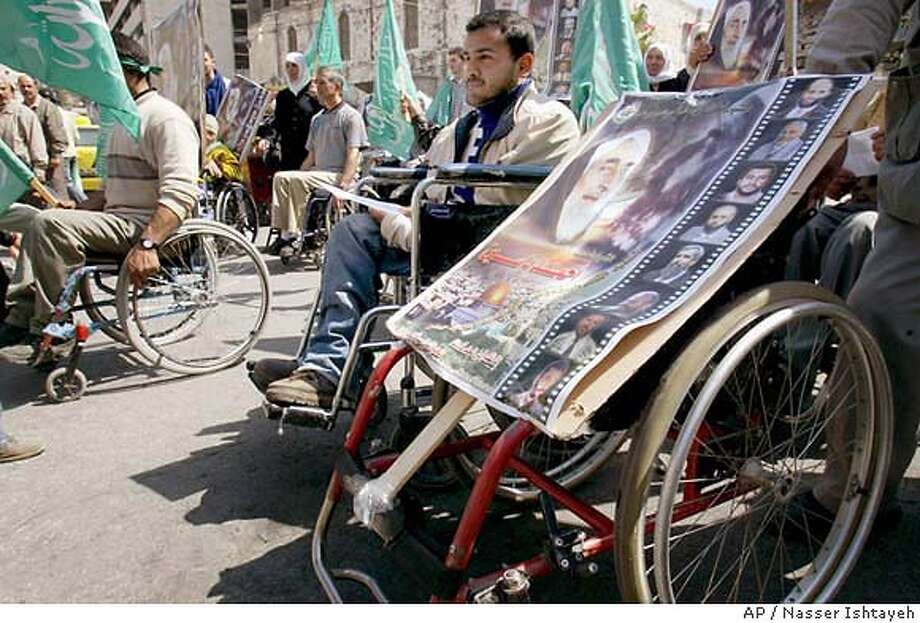 Wheelchair-bound Palestinians hold posters of Hamas founder Sheik Ahmed Yassin as they demonstrate in the West Bank city of Nablus Thursday, March 25, 2004. Sixty prominent Palestinian officials and intellectuals on Thursday urged the public to refrain from retaliation for Israel's assassination of Hamas' founder, saying it would ignite a new round of bloodshed that would only hurt Palestinian aspirations for independence. (AP Photo/Nasser Ishtayeh) Photo: NASSER ISHTAYEH