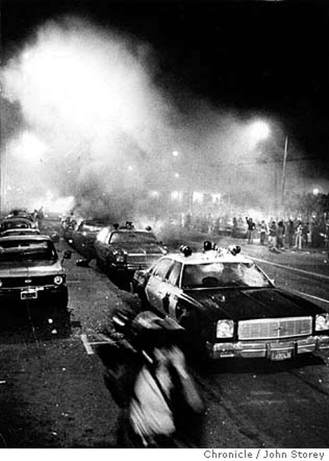 WHITE NIGHT/22MAY79/MN/STOREY - OVERALL OF THE POLICE CARS ON FIRE AT CIVIC CENTER. THE PERSON IN THE FOREGROUND WAS A NEWS CAMERAPERSON RUNNING. THE RIOT STARTED AFTER THE VERDICT FOR DAN WHITE CAME DOWN FROM THE COURT. RIOTS STARTED UP OUTSIDE CIVIC CENTER, NEAR CITY HALL. Dan White, George Moscone, Harvey Milk. CHRONICLE PHOTO BY JOHN STOREY/1979 Photo: JOHN STOREY