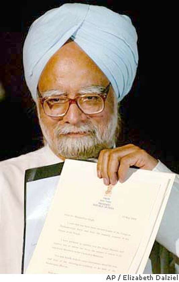 Manmohan Singh holds an invitation from the Indian President A. P.J. Abdul Kalam, who instructed Singh to form the new government, at the Presidential Palace in New Delhi, India, Wednesday, May 19, 2004. Manmohan Singh, the architect of India's economic reforms and a respected consensus builder, was named prime minister of India on Wednesday, ending weeks of political turmoil that culminated with Sonia Gandhi's stunning refusal to take the post. (AP Photo/Elizabeth Dalziel) Photo: ELIZABETH DALZIEL